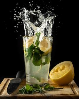 Spruzzi di limonata con menta e limoni sul tavolo isolato su un nero
