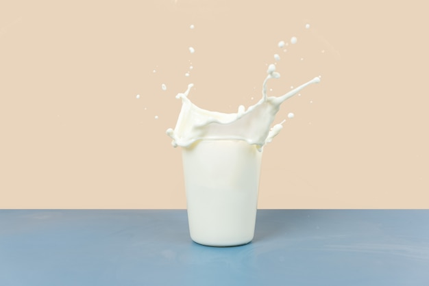 The splashing milk in the cup is against a yellow and gray background