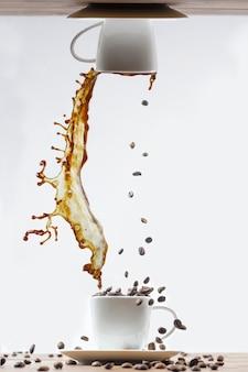 Брызги кофе в белой чашке и падающие кофейные зерна на белом фоне.