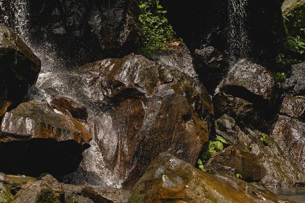 튀는 물. 전경에 있는 젖은 바위에 초점을 맞춘 사진, 폭포 방울