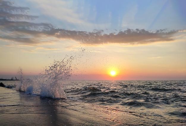 Брызги волны на море на фоне заката природы