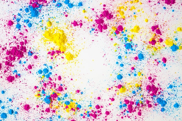 Splatter of yellow; pink and blue holi color powder on white background
