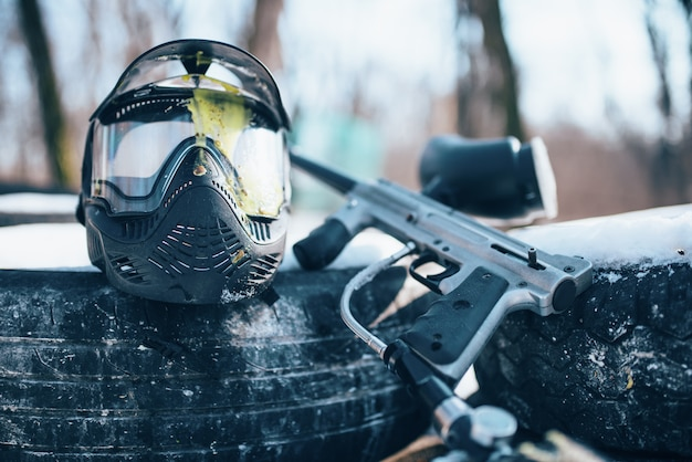 Splattered paintball mask with glasses and marker gun closeup, nobody. extreme game equipment, sport ammunition