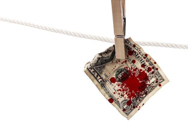 Обрызганная кровью банкнота доллара сша вешается на веревку с прищепкой. понятие о незаконных и преступных заработках.