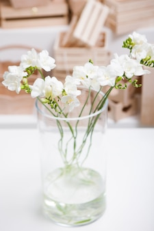 Splendid bunch of white orchid in glass vase on table and wooden boxes background. floristics workshop, floral arrangement for presents, tenderness in interior and decoration concept