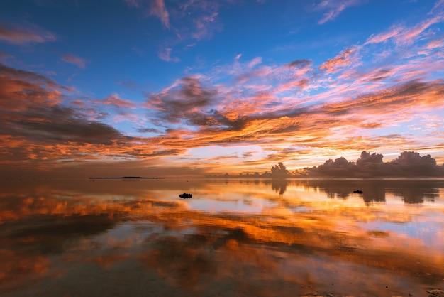 鮮やかな色とりどりの日の出、鏡のように滑らかな海面に映る黄色、オレンジ、ピンク、ブルーの雲。