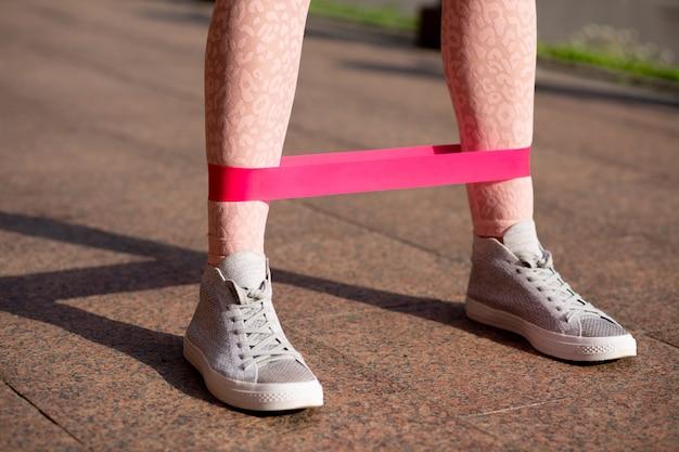 公園でゴム製の抵抗バンドで脚のトレーニングをしている見事なフィットの女性