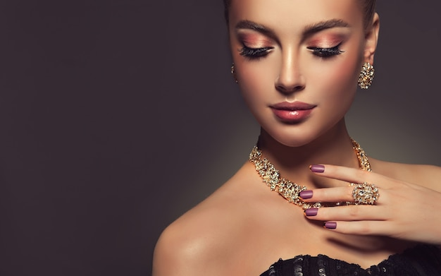 Splendid makeup with long black eyelashes and dark rose lipstick on the face of pretty woman french manicure on her nailscloseup portrait of beautiful model dressed in a gilded jewellery set