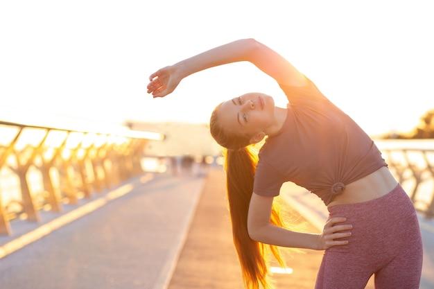 太陽の光の中で橋でトレーニングの前に暖まる見事な赤い髪の若い女性。テキスト用のスペース Premium写真