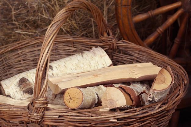 Split birch logs lie in a wicker basket