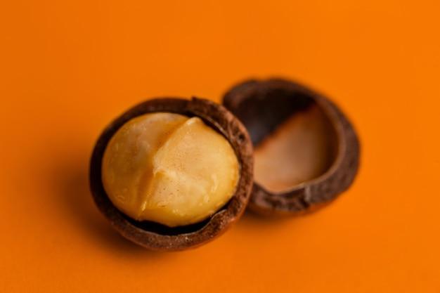 オレンジ色の背景にマカダミアナッツのクローズアップを分割