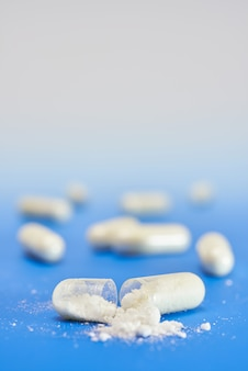 Split open transparent capsule with white powder on blue