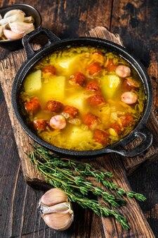 鍋にスモークソーセージを入れたエンドウ豆のスープを割る