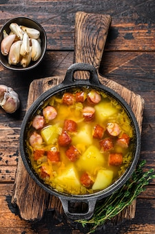 Split pea soup with smoked sausages in a pan