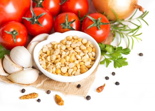 ボウルに黄色のエンドウ豆を分割し、白で隔離生野菜をクローズアップ