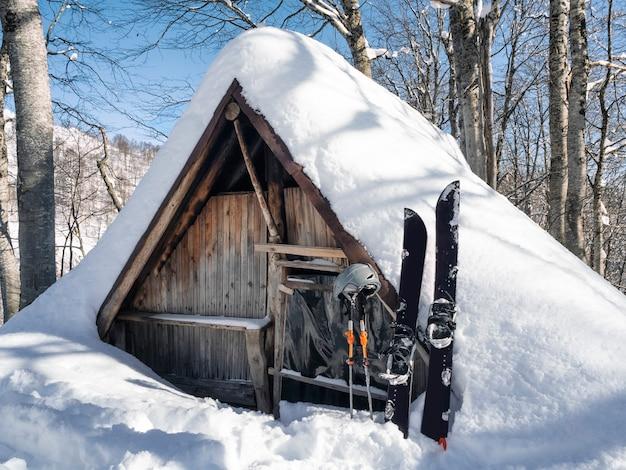 양치기의 목조 주택에서 스플릿보드와 기둥이 배경을 흘려 스키 투어를 위한 스포츠 장비
