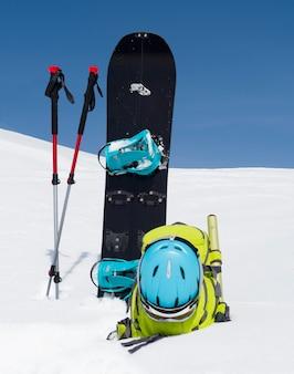 雪と青空を背景に、スプリットボード、トレッキングポール、バックパック。スキーツーリング用具