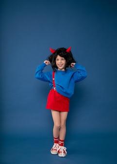 Избалованный ребенок, непослушная девочка, детские капризы. красивая маленькая девочка в парике с красными рогами чертенка, показывающими характер. концепция детской кризисной психологии. фото в полный рост