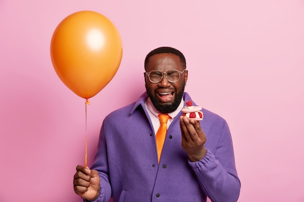 甘やかされて育った休日の概念。紫色のジャケットで泣いているひげを生やした男は、否定的な感情を表現します