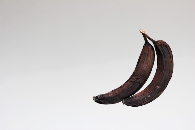 Испорченные старые бананы. два гнилых почерневших и высушенных банана.