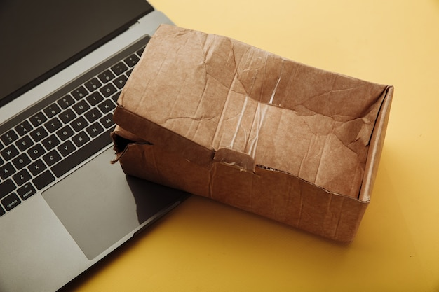 Spoiled paper box and laptop. online shopping and delivery concept. shipment accident