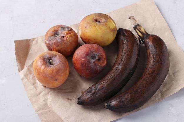 곰팡이가 있는 버릇없는 썩은 음식:회색 배경에 사과와 바나나. 확대.