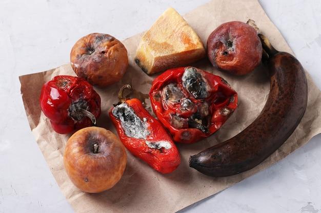 Испорченные гнилые продукты с плесенью: яблоки, перец, твердый сыр и банан на сером фоне, крупным планом