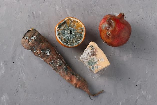 곰팡이가 있는 썩은 음식:회색 배경에 오렌지 반, 석류, 당근, 단단한 치즈, 위쪽