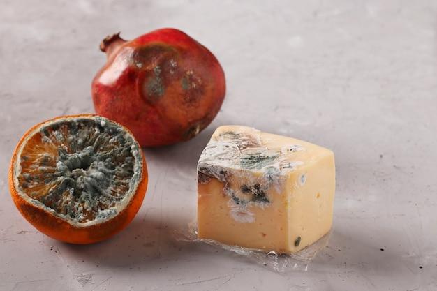 곰팡이가 있는 버릇없는 썩은 음식:석류, 회색 배경에 오렌지 반, 단단한 치즈, 클로즈업