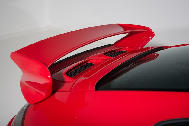 Spoiler of a red sports car in a white room