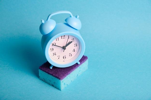 スポンジと目覚まし時計の春の大掃除のコンセプト