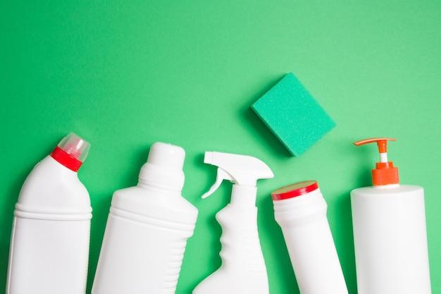 Бутылки с губкой и моющим средством без этикеток на зеленом фоне с копией пространства