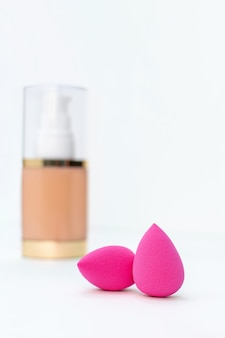 Sponge and a bottle of beige cosmetic foundation for make-up. makeup artist accessories for perfect face skin