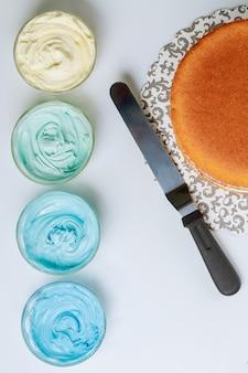 へらで青いアイシングで飾る前のスポンジケーキ。