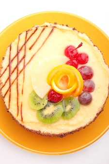 Sponge cake decorated with icing and fruit on a white background