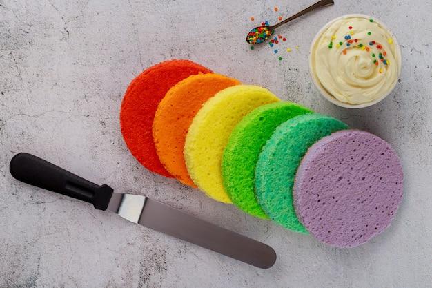 バースデーケーキを作るためのスポンジケーキ、フロスティング、ヘラ。