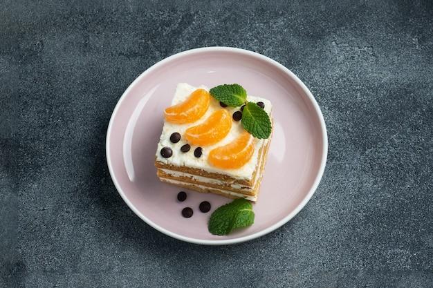 버터 크림을 곁들인 스폰지 케이크 레이어, 귤 초콜릿과 민트 조각으로 장식. 차에 대한 맛있는 달콤한 디저트. 상위 뷰, 복사 공간.
