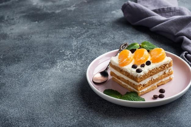 버터 크림을 곁들인 스폰지 케이크 층, 귤 초콜릿과 민트 조각으로 장식. 차 맛있는 달콤한 디저트. 상위 뷰, 복사 공간.