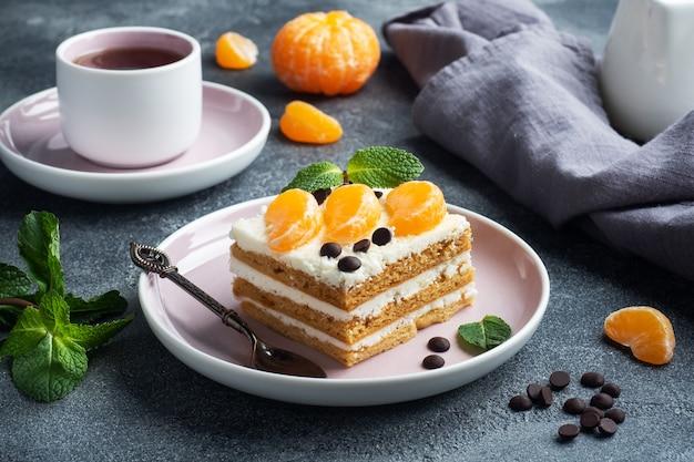 버터 크림을 곁들인 스폰지 케이크 층, 귤 초콜릿과 민트 조각으로 장식. 차 맛있는 달콤한 디저트.
