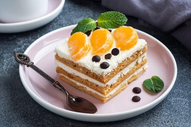 버터 크림을 곁들인 스폰지 케이크 레이어, 귤 초콜릿과 민트 조각으로 장식. 차에 대한 맛있는 달콤한 디저트.