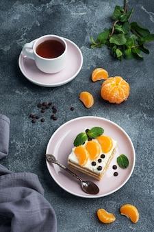 Коржи бисквитные со сливочным кремом, украшенные дольками мандаринового шоколада и мятой. вкусный сладкий десерт к чаю.