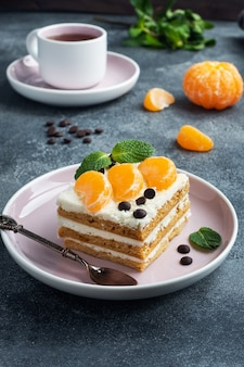 タンジェリンチョコレートとミントのスライスで飾られたバタークリームとスポンジケーキの層。お茶にぴったりの美味しいスイーツ。