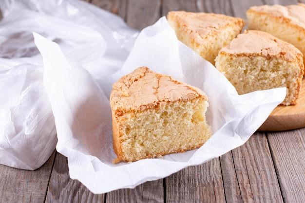 スポンジケーキ。後で使用するために冷凍する準備ができているナプキンまたはバッグに包まれたパイの一部。