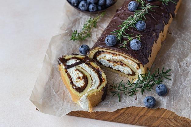 Бисквитный рулет с шоколадом и сливочным сыром с шоколадной глазурью, черникой и розмарином.