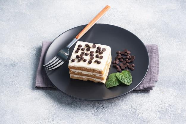 黒いプレートにバタークリームとチョコレートのかけらがミントになったスポンジケーキ。イベントや誕生日パーティーを祝うためのデザート。上面図、コピースペース。