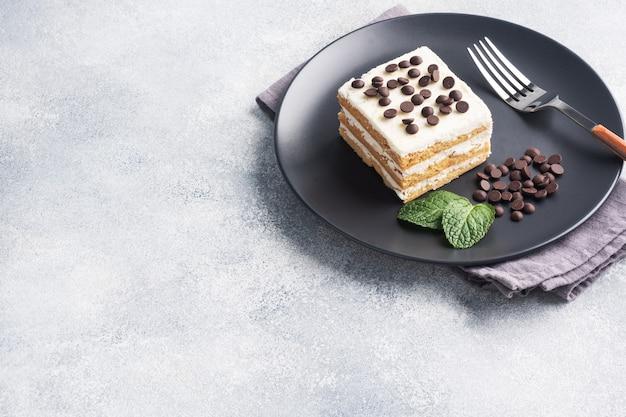Buttercream와 초콜릿 조각 스펀지 케이크 검정 잉크 판에 민트. 축하 이벤트 또는 생일 파티를위한 디저트. 평면도.