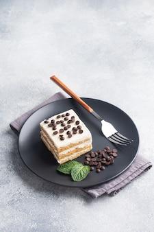 黒いプレートにバタークリームとチョコレートのかけらがミントになったスポンジケーキ。イベントや誕生日パーティーを祝うためのデザート。上面図。