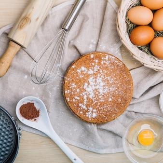 Pan di spagna con zucchero a velo e ingredienti sul tavolo di legno