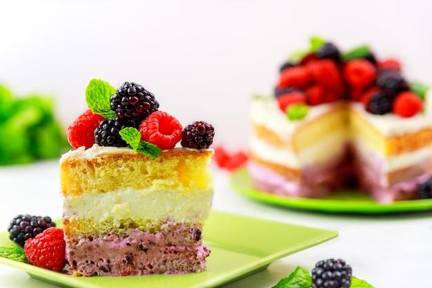 Бисквит с ванильным кремом и свежими ягодами на белом столе.
