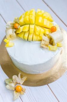 白いクリームと白い木製のテーブルにマンゴーの大きな装飾的な部分のスポンジケーキ